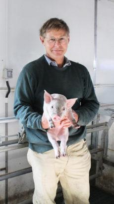 Mr Robert Lasseter holding a piglet
